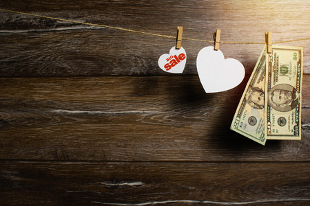 Two hearts and dollar banknotes drying on the clothesline by clothespins on wooden background. Spring sale