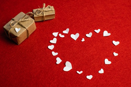 Beautiful heart made from small white paper heart sand two gifts with bows isolated on red. Feast of Saint Valentine