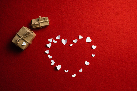 Romantic symbol of love in the form of a heart, handmade cutouts from white paper and two gifts. The day of lovers