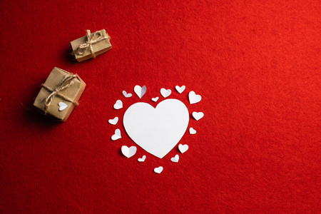 White heart cutted from paper and a lot of smaller hearts around it over red background. Atmosphere of love