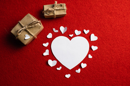 Love decoration of white paper hearts surrounded by big heart and two present boxes on red background. St. Valentine's day Standard-Bild
