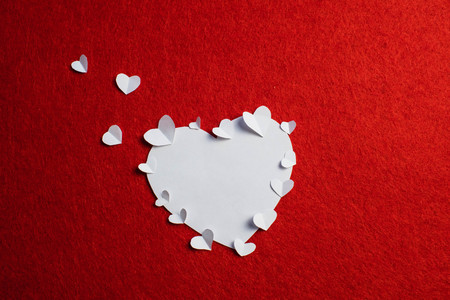 Heart shaped white paper and a lot of smaller hearts on it in red background. Romantic atmosphere on Valentines day