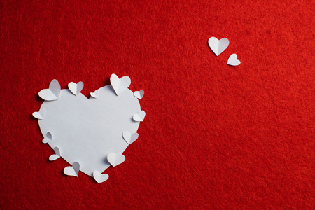 White paper heart and many small paper hearts on periphery of it over the red background. Saint Valentine's day