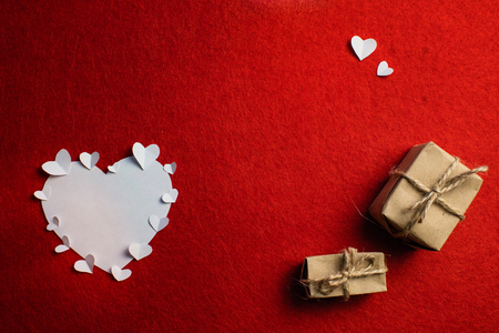 Valentine day composition: small paper hearts encircle big white heart and and two gift boxes with bows on a red background