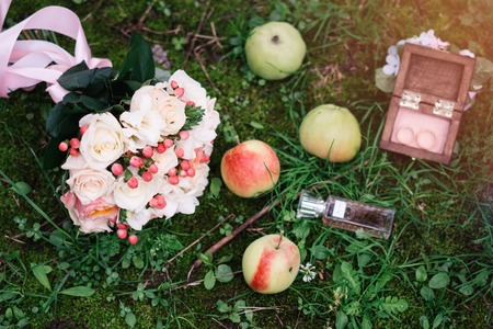 wedding bouquet of white roses in green grass with apples and wedding rings Standard-Bild