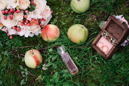 wedding rings in a wooden box in the grass with apples and perfumes with a wedding bouquet of flowers Standard-Bild