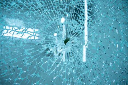 Broken window glass with blue background. Standard-Bild