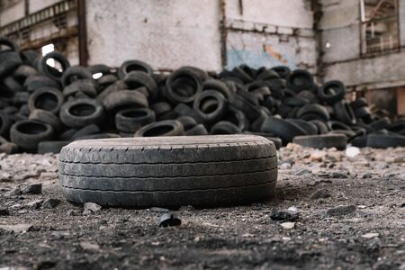 old car tire lying on the ground of an abandoned factory compared to other tires.