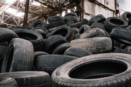 A pile of old rotten rubber tires on the ruined building background. Standard-Bild