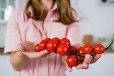 A large branch of red cherry tomato in the hands of a girl