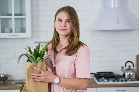 Girl in the kitchen with an ecological paper bag of purchased food