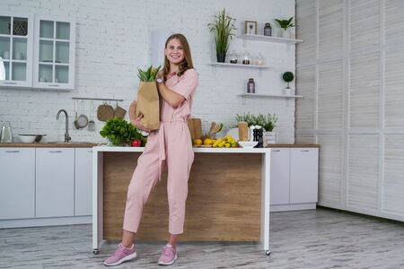 Woman with pack of fruits and vegetables in the kitchen Standard-Bild
