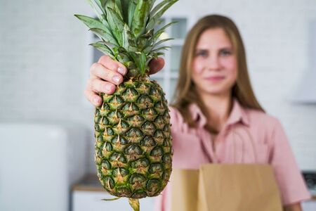The girl in the pink blouse holds a large pineapple in her hand. Healthy eating Standard-Bild