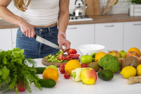 Female hands chopped fruit and vegetable salad for a healthy diet breakfast. Colorful Vegetarian Products