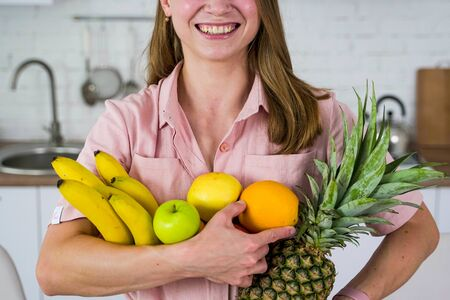 A young girl with a smile holds fruit in her hands. Healthy eating vegans.