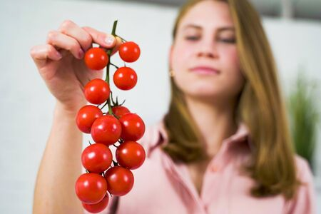 A woman in the kitchen is holding a hanging branch of red cherry tomato. Organic vegetables for a healthy lifestyle