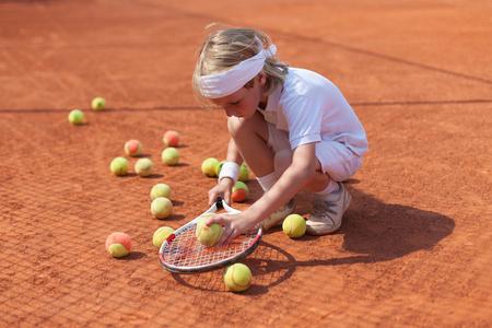 jugando tenis: niño practicando el tenis