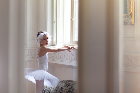 looking at young ballerina through the doors