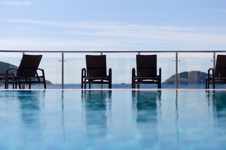 glass fence: loungers by the pool