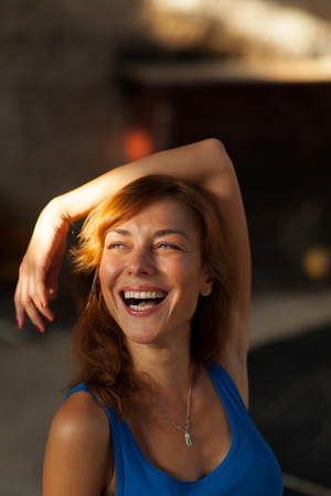 beautiful young woman looking at a ray of sunlight and smiling