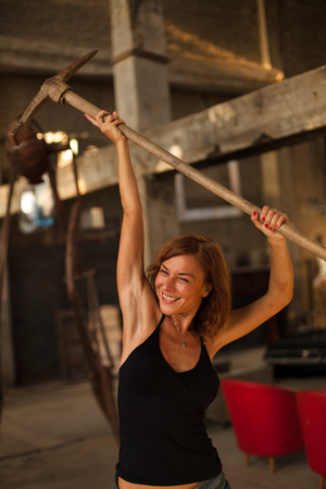 beautiful young woman posing with pickax