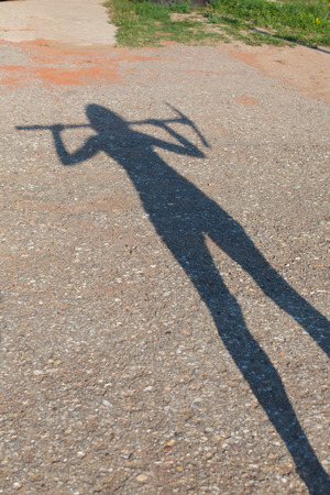 silhouette of a woman holding a pickax