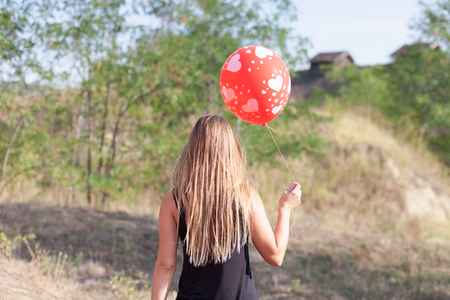 behind view of young woman with balloon