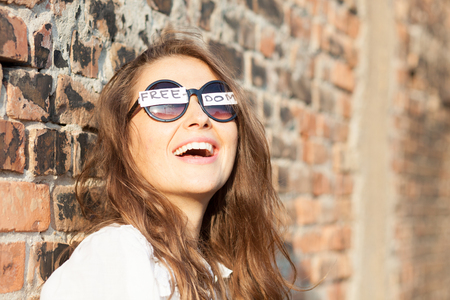 young woman with freedom sign on sunglasses