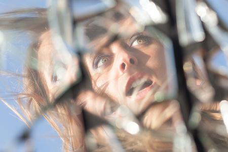 woman reflection in broken mirror Stock Photo