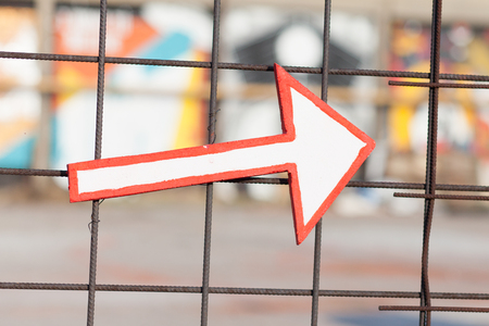 white arrow with red outline attached on fence pointing to the right Stock Photo