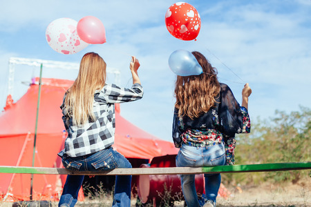 two young women with balloons in front of a circus tent