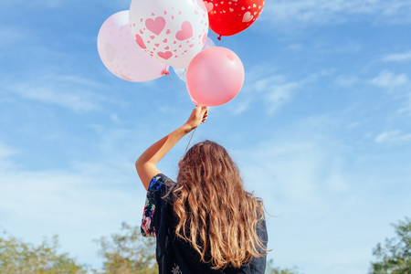 young woman with many balloons walking
