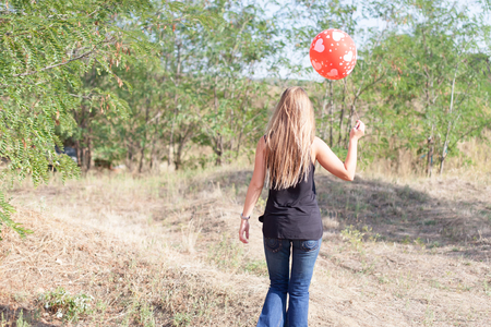 behind view of young woman walking with balloon
