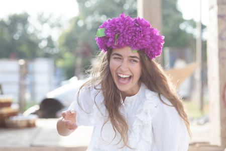 smiling hipster girl with flower wreath on head