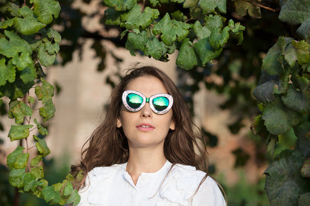 Young woman with sunglasses standing under leaves