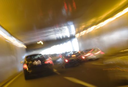 drunken: Motion blurred cars at the end of a tunnel Stock Photo