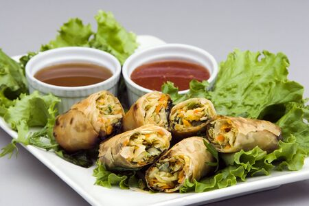Vegetarian Spring Rolls on a bed of lettuce with dipping sauces  Stock Photo