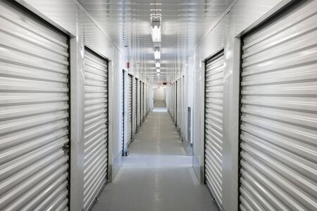 A perspective view down a corridor of storage units Imagens