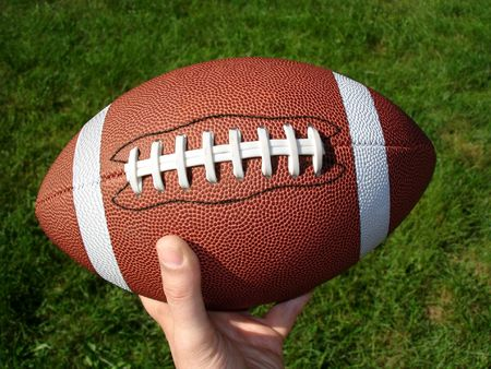View of a hand holding football in the sun against a green background.