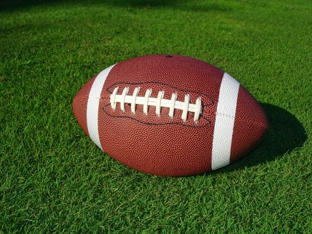 Closeup view of a football on short grass in the sun.