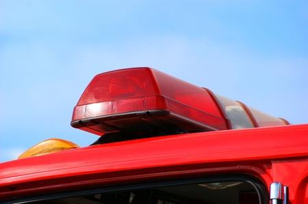 camion pompier: Gros plan de feu camion haut lumi�res sur fond de ciel bleu. Banque d'images