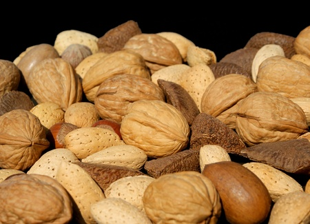 Angled view of assorted nuts against black background.