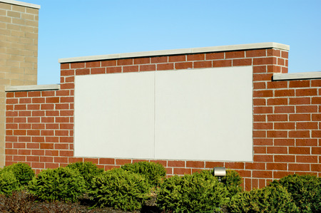 Blank brick sign area in white with blue sky background and shrubs in foreground. Allows for adding custom letters and message.