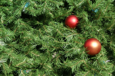 Closeup view of a Christmas tree with ornaments and lights. Ideal for use as a background. Stock Photo