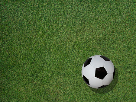 View of a classic soccer ball on green sports turf grass. Stock Photo