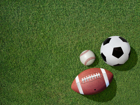 View  of sports equipment including baseball, soccer and football on grass background.
