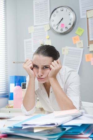 messy desk: Tired frustrated female office worker at desk looking at camera. Stock Photo