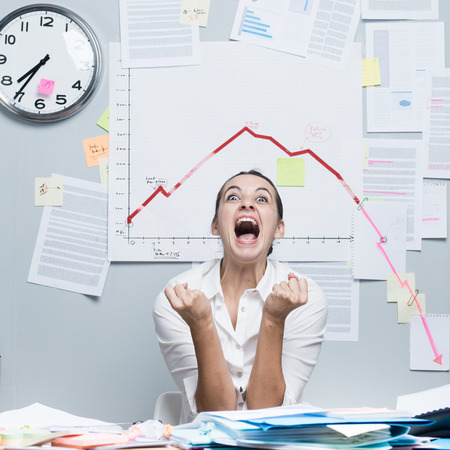 Shocked businesswoman screaming under financial negative diagram with arrow going down. photo