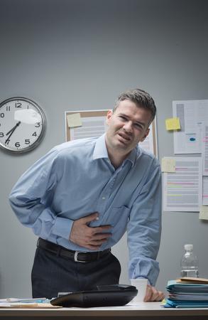 Souligné d'affaires avec des maux d'estomac se penchant à son bureau. Banque d'images - 33146885