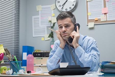 Vermoeide beklemtoonde zakenman op de telefoon op zijn bureau. Stockfoto